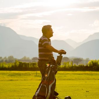 Golfer with his golf bag on the fairway with sunshine in Switzerland.