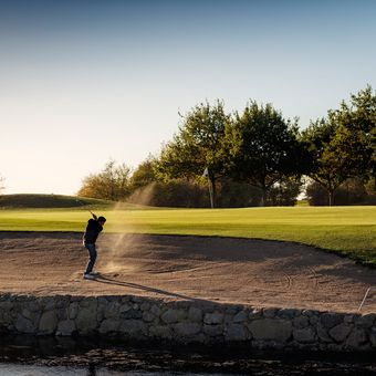 Portrait of a golfer as he hits a perfect bunker shot out of the sand. Photographed in the late autumn sunlight  on a course on the island of Møn in Denmark. Colour, horizontal with some copy space.